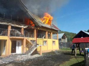 Fânar şi casă cuprinse de flăcări